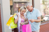 Happy mature couple looking at their shopping purchases — Stock Photo