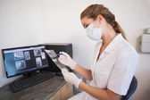Dental assistant looking at x-rays on computer — Stock Photo
