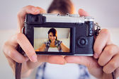 Pretty brunette taking a selfie with retro camera on couch — Stock Photo
