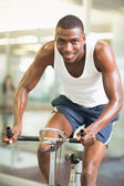 Portrait of man working out on exercise bike at gym — Foto Stock