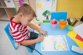 Cute little boy drawing at desk — Stock Photo
