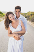 Loving couple standing on countryside road — Stock Photo