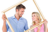 Attractive young couple holding picture frame — Stock Photo