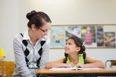 Teacher helping pupil in classroom — Stock Photo
