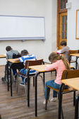 Pupils writing at desks in classroom — Stock Photo