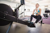 Full length of tired woman sitting in gym — Stock Photo