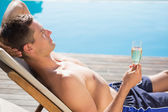 Man holding champagne by the swimming pool — Stock Photo