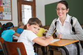 Teacher helping pupil in classroom — Stockfoto