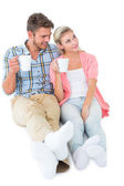 Attractive young couple sitting holding mugs — Stockfoto