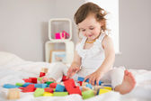 Cute girl playing with building blocks on bed — Stock Photo