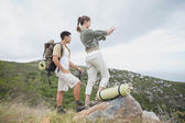 Hiking couple standing on mountain terrain — Stock Photo