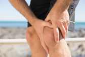 Fit man gripping his injured knee — Stockfoto