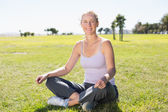 Fit mature woman sitting in lotus pose on the grass — Stock Photo