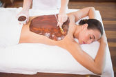 Attractive woman receiving chocolate back mask at spa center — Стоковое фото
