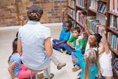 Pupils and teacher having class in library — Stock Photo