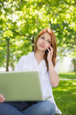 Redhead using her laptop while phoning — Stock Photo