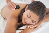 Brunette enjoying hot stone massage — Foto de Stock