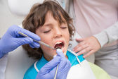 Pediatric dentist examining a little boys teeth — Stock Photo