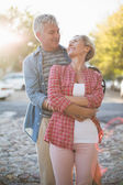 Happy mature couple hugging in the city — Stock Photo