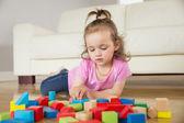 Girl playing with building blocks on floor — Stock Photo
