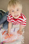 Cute little schoolboy smiling at camera while drawing — Stock Photo