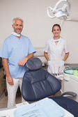 Dentist and assistant smiling at camera — Stock Photo