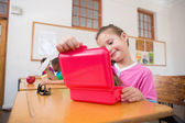 Pupil opening lunchbox in classroom — Stock Photo