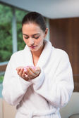 Woman in bathrobe holding flowers in spa — Stock Photo