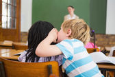 Pupils whispering secrets during class — Stock Photo