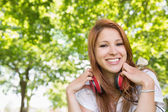 Redhead listening to music in the park — Stock Photo