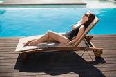 Beautiful woman in bikini relaxing by swimming pool — Stock Photo