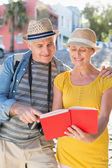 Happy tourist couple using guide book in the city — Stock Photo