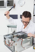 Angry computer engineer holding hammer — Stock Photo