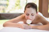 Beautiful woman holding flower on massage table at spa center — Stock Photo