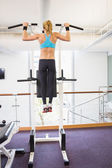 Rear view of fit woman doing pull ups at gym — Stock Photo