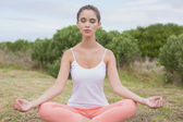 Woman sitting in lotus position on countryside landscape — Stockfoto