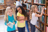 Pupils and teacher looking for books — Stock Photo