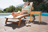 Woman relaxing on sun lounger by swimming pool — Stock Photo
