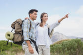 Couple pointing and smiling on country terrain — Stock Photo