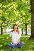 Pretty redhead smiling at camera in the park — Stock Photo