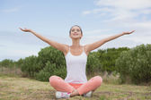 Woman sitting with arms raised on countryside landscape — Stock Photo