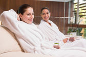 Smiling women in bathrobes sitting on couch — Stock fotografie