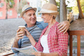 Gelukkig toeristische paar koffie drinken op een bankje in de stad — Stockfoto