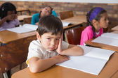 Bored pupil sitting at his desk — Stock Photo
