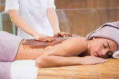Attractive woman receiving chocolate back mask at spa center — Stock Photo
