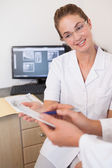 Dentist and assistant studying x-rays on computer — Stock Photo