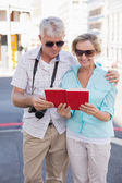 Happy tourist couple using tour guide book in the city — Stockfoto