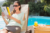 Woman reading book by pool with breakfast on table — Stock Photo