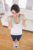 Fit brunette on the weighing scales — Stock Photo