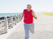 Fit mature man jogging on the pier — Stockfoto